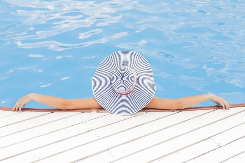 Back of person in large sun hat relaxing in pool