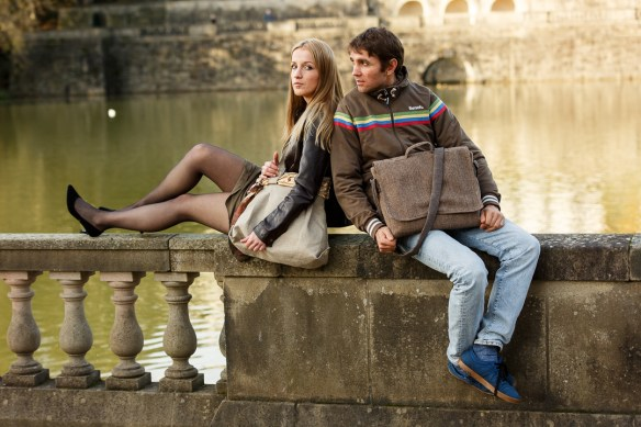Messenger bag. Girl and boy sat on wall next to river. Both have a bag
