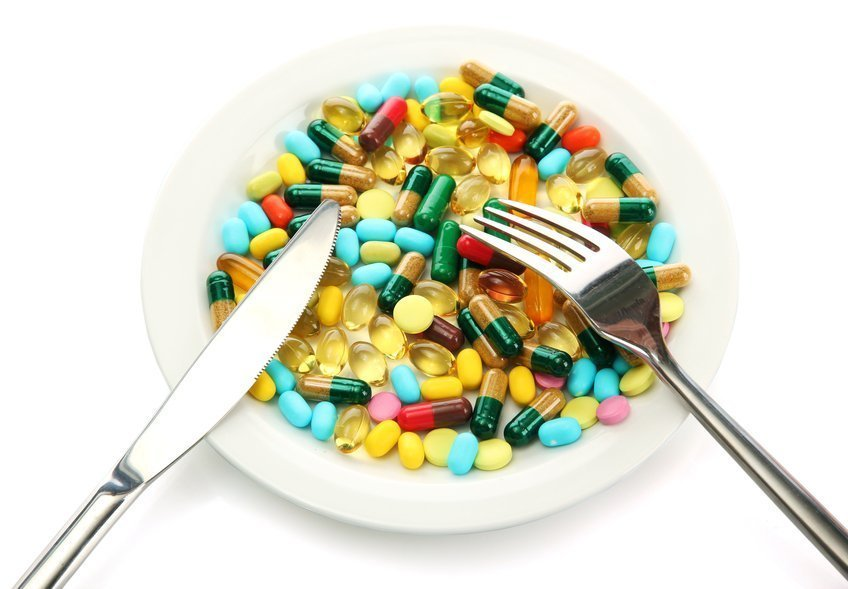 Colorful capsules and pills on plate with fork and knife, isolated on white