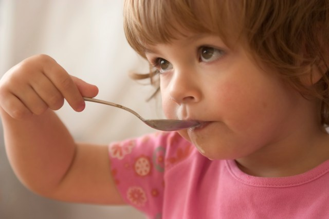 hungry child eating meal with a spoon