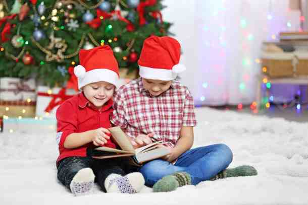Two boys reading book on Christmas decoration background