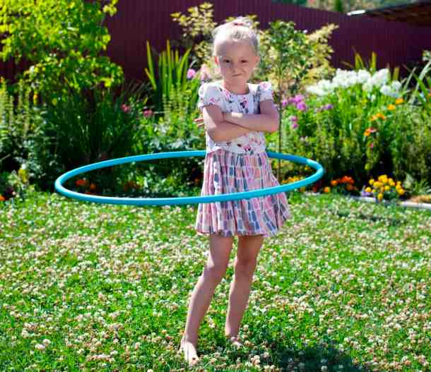 Little girl playing with hula hoop in her garden
