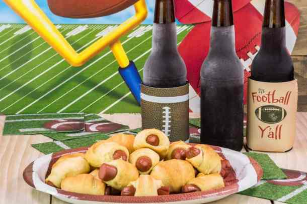 Bottles of cold beer and plate with pigs in blanket on the table