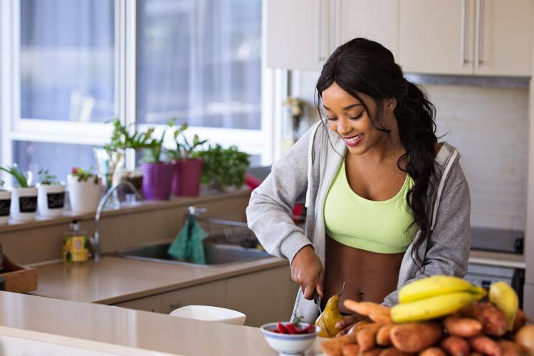 10 ways to slow signs of ageing around your eyes without using an eye cream. Image of a young woman cutting fruit in a kitchen during the day