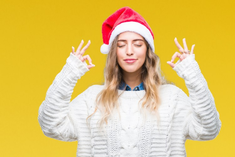 How to have a happier Christmas: Image of a young blonde woman wearing christmas hat over isolated background relax and smiling with eyes closed doing meditation gesture with fingers. Yoga concept.