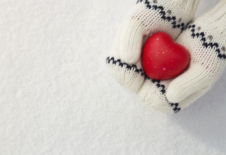 How to have a happier Christmas.  Image of Winter background, close up of little girls hands holding red rubber heart with copy space