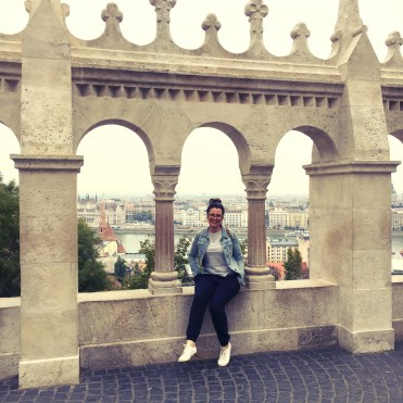 5 Things to do in Buda, Budapest. Image of Alex Grace sitting on a wall underneath an arch with a view of Pest in the background at Fisherman's Bastion