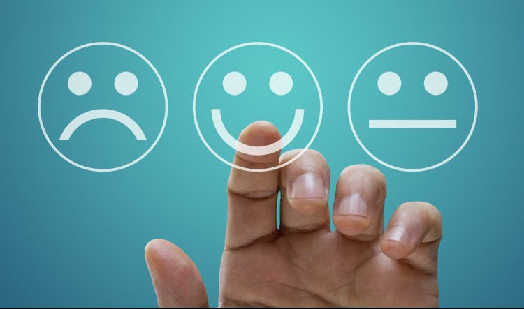 Improving well-being: The key to being happy?  Image of 3 emoticon faces, unhappy, happy and unsure/OK a hand is held up about to select the happy emoticon