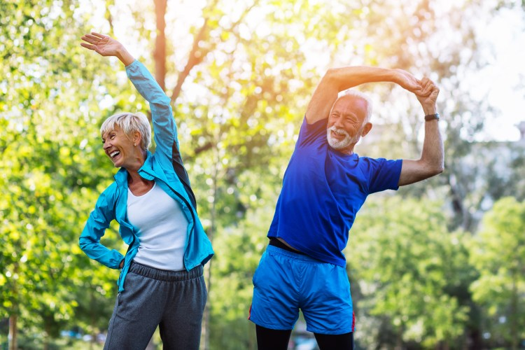 Improving well-being: The key to being happy? Image of happy fit senior couple exercising in park