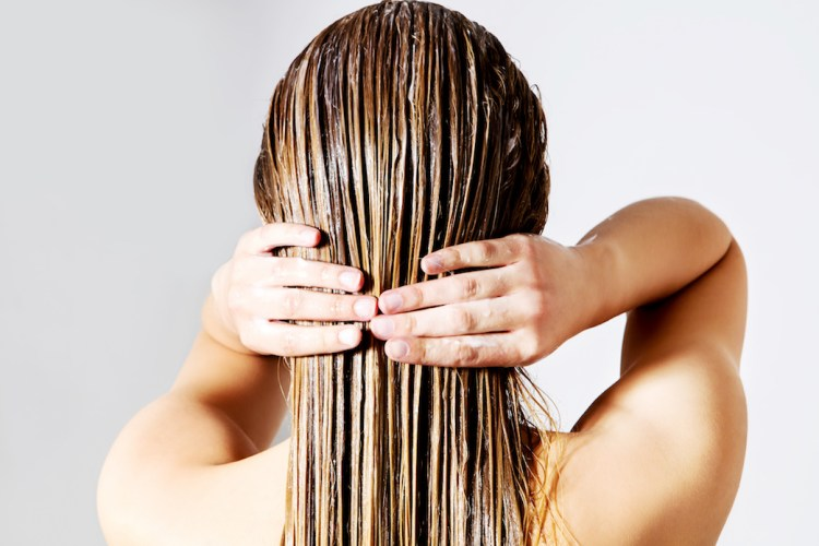 For the scrub of it: why should you exfoliate and how to do it right. Image of Blond woman applying hair conditioner. Isolated on white.
