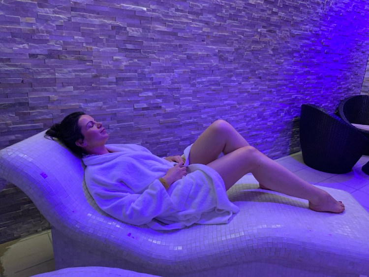 The rise of the leisure centre day spa (Verulamium Spa, St Albans) Image of Alex Grace  relaxing in a spa robe on a heated bench within the Verulamium Spa, St Albans.