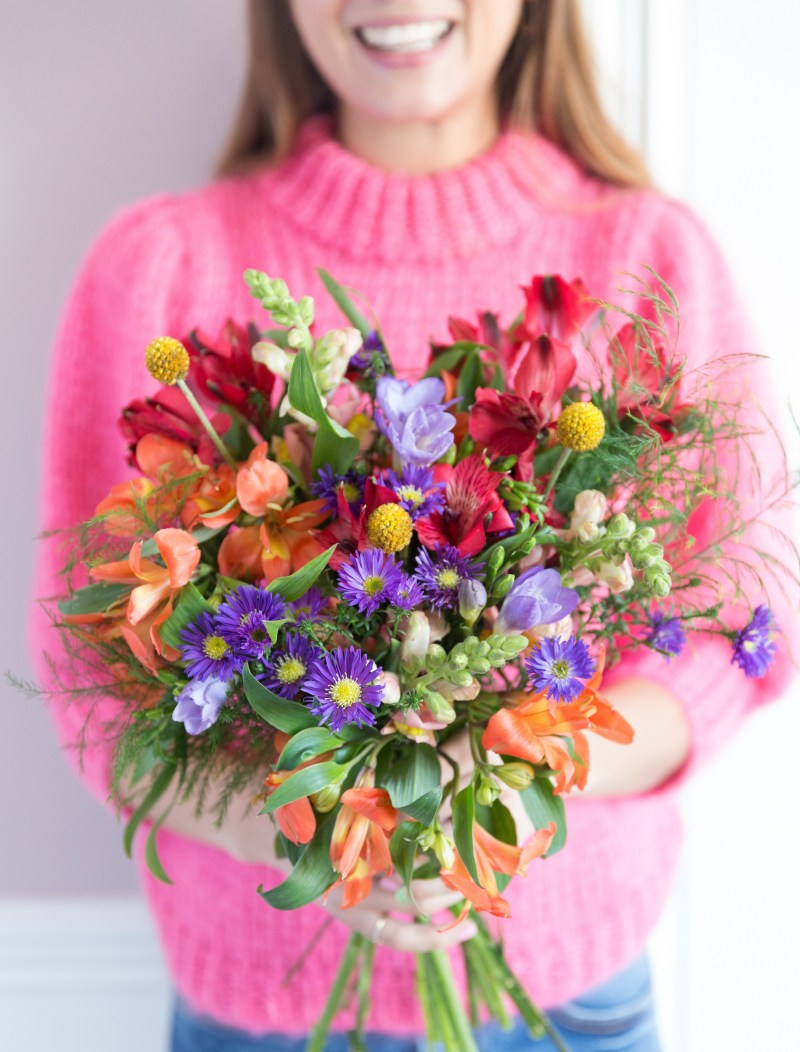 Blooming lovely: the positive power of flowers. Image of a smiling woman holding a hand-tied bouquet of flowers