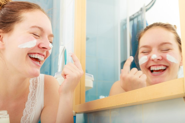 How to get the most out of your skincare products. Happy young woman applying cleansing moisturizing skin cream on face.