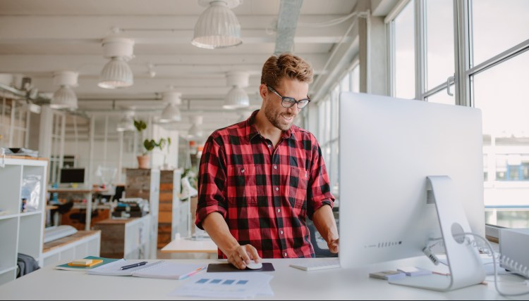 Exercise Hacks: How to be fitter without really trying. Image of Shot of happy young man standing up working on desktop computer in modern workplace.