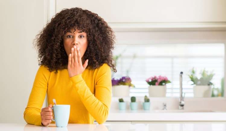 What to do when you make a mistake (in any area of your life) Beautiful African American woman holding a cup of coffee at home cover mouth with hand shocked with shame for mistake, expression of fear, scared in silence, secret concept (image description taken from Adobe Stock)