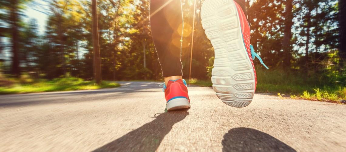 How to start running: Tips for beginner runners. Image of Female runner jogging down the road at sunset