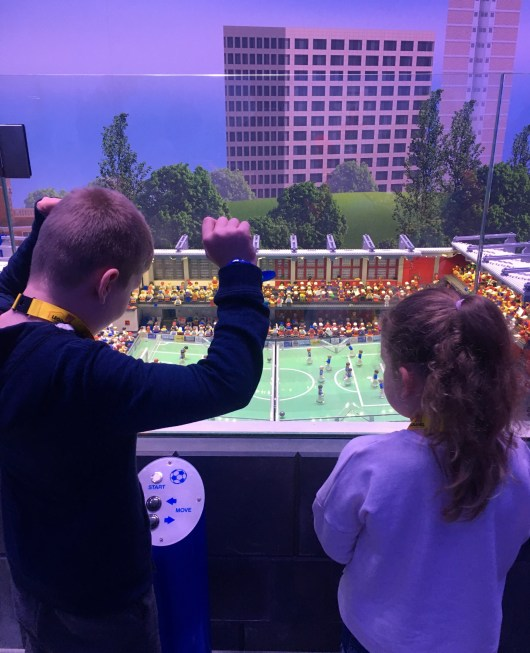 Happy Days: Legoland Discovery Centre Birmingham. Image of a young boy and girl looking at the Miniland football match at Legoland Discovery Centre Birmingham