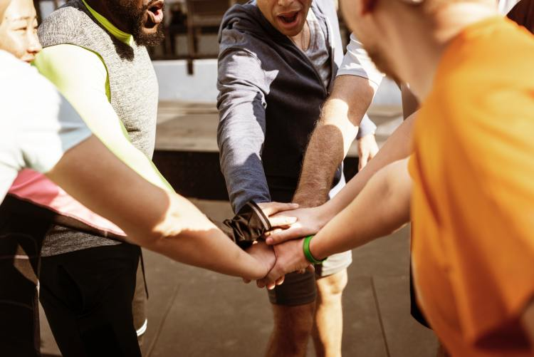 How to keep your running motivation.  Image of a group of people putting their hands into a circle to celebrate a work out