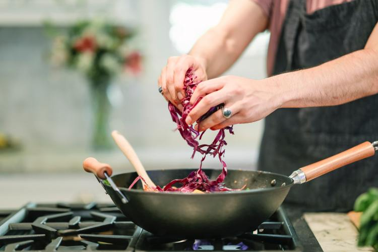 Exercise Hacks: How to be fitter without really trying. Image of an adult male putting shredded red cabbage into a wok cooking on a stove