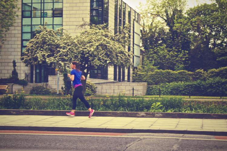 How to start running: tips for beginner runners. Image of woman running along city road