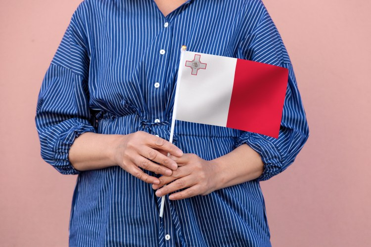 10 Things you should know about Malta. Going to Malta - 10 things you need to know. Image of Malta flag. Close up of woman's hands holding Maltese flag.