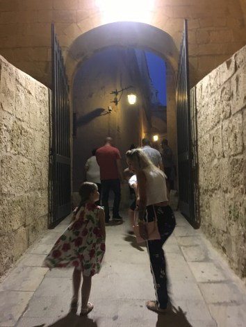 Happy Travels: Where you absolutely should go in Malta. Image of people entering Mdina at night
