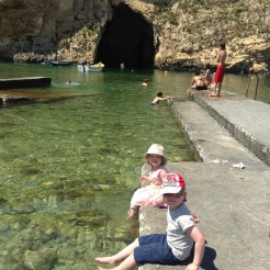 Happy Travels: Where you absolutely should go in Malta. Image of 2 young children paddling their feet at Dwejra Bay Gozo