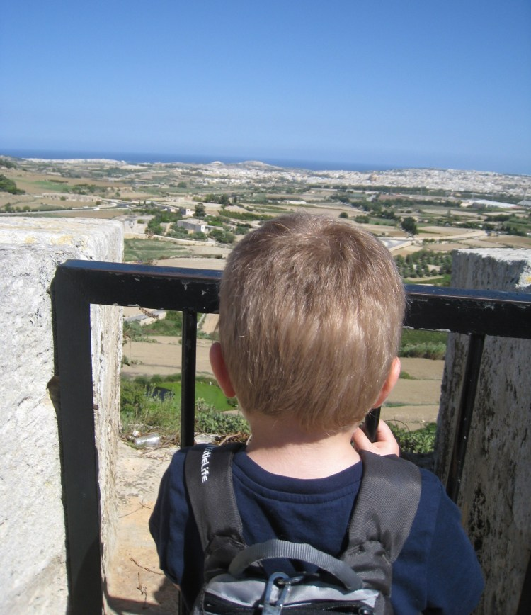 Happy Travels: Where you absolutely should go in Malta. Image of the back of a young boy at the citadel walls in Mdina