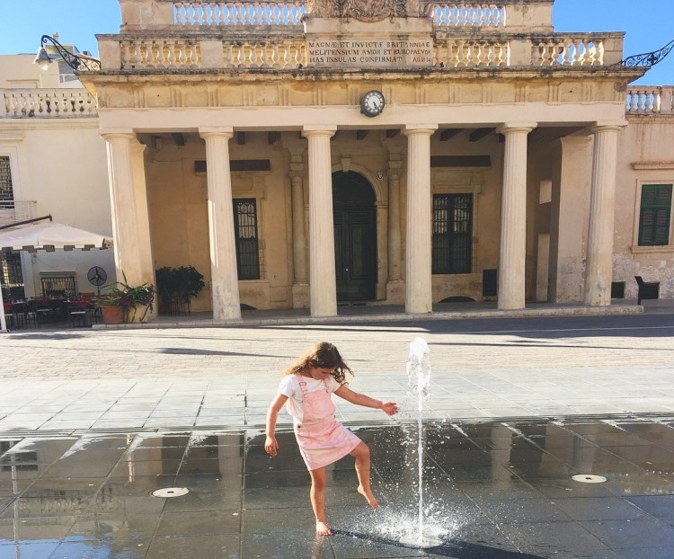 Fun things to do in Malta with kids. Image of young girl playing by a water fountain in Valletta Malta.