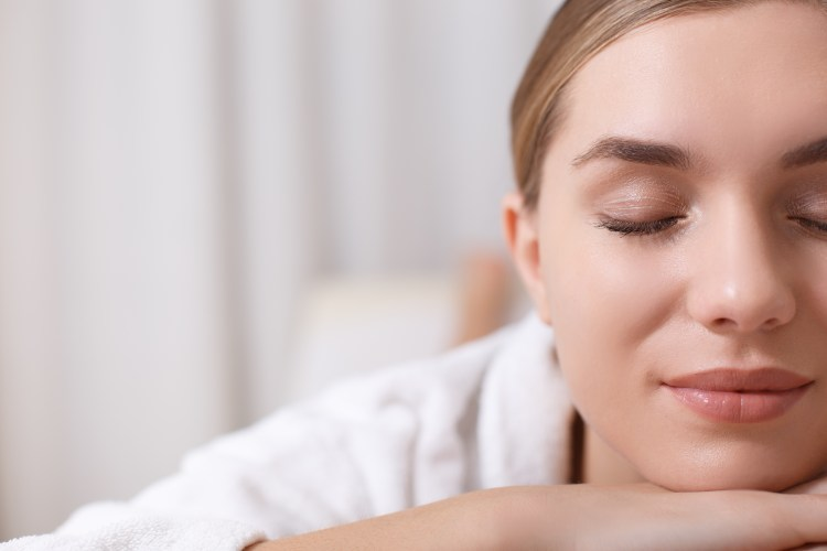 benefits of a spa day and spa tips. Image of Close up of half of female face. Serene young woman is lying at wellness center with relaxation.