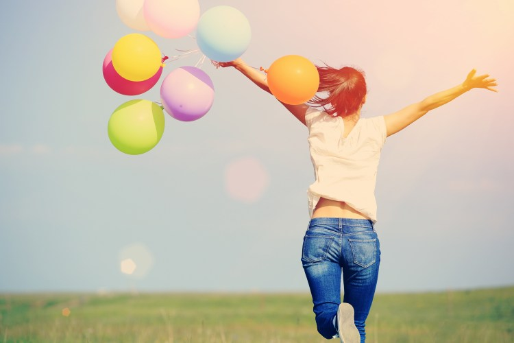 Catastrophe to calmness:  A technique to calm your worrying thoughts.  How to stop catastrophizing.  Image of your woman running through a field holding a bunch of balloons