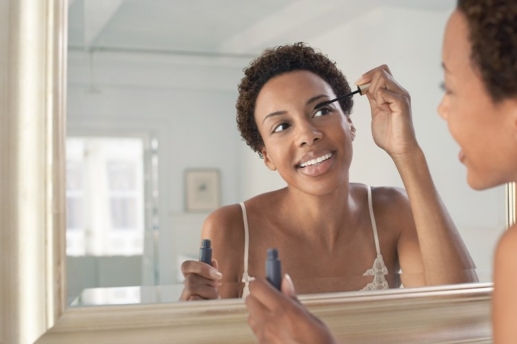 5 minute makeup routine. How to do your makeup in only 5 minutes. Image of Closeup of an African American woman applying mascara in mirror at home