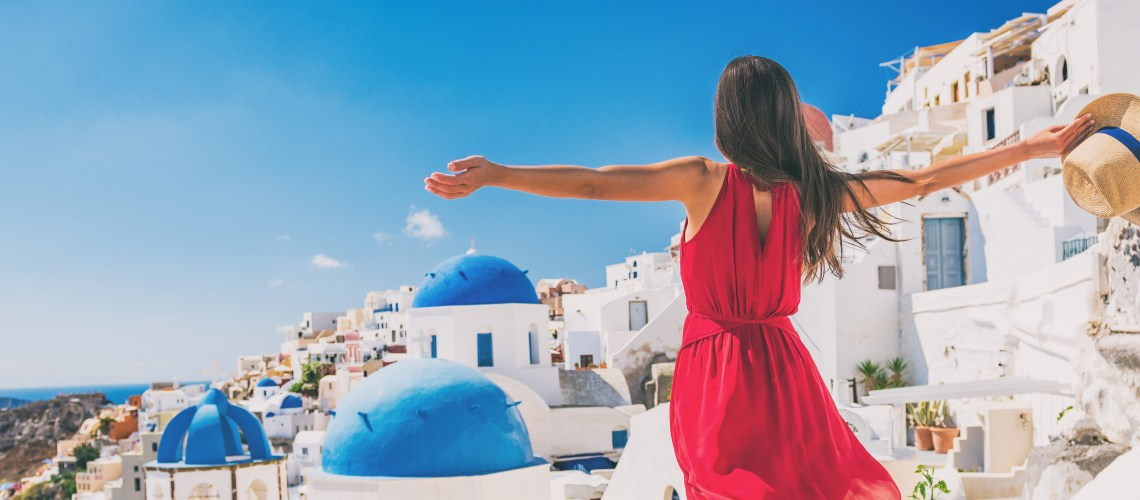 Happy Holidays: How to make your holiday even happier. Feel happy on holiday. Image of Europe travel vacation fun summer woman feeling free dancing with arms open in freedom at Oia, Santorini, Greece island. Carefree girl tourist banner panorama.