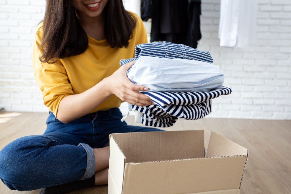 How can clothes make you happy? Plus expert tips for more successful shopping. Image of woman putting folded clothes into a box to donate to charity