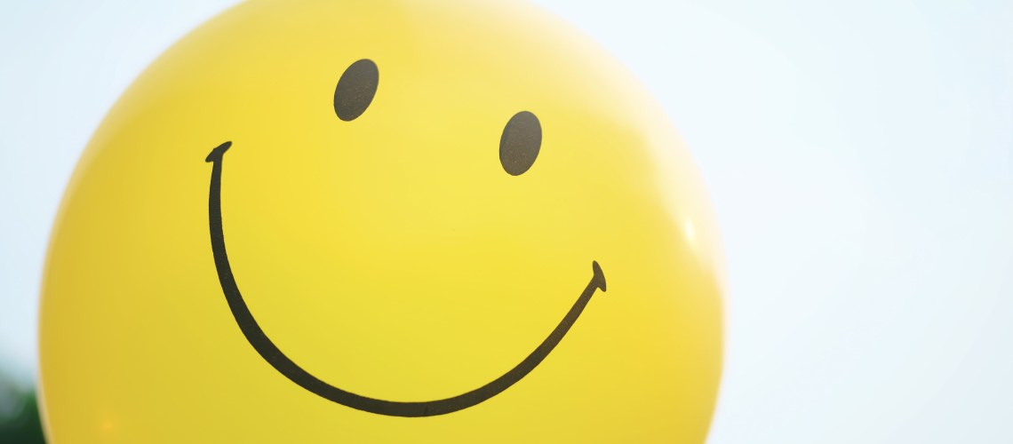 Smile! Everything you need to know (but didn't realise) about smiling. Image of a yellow balloon with a smiling face on it