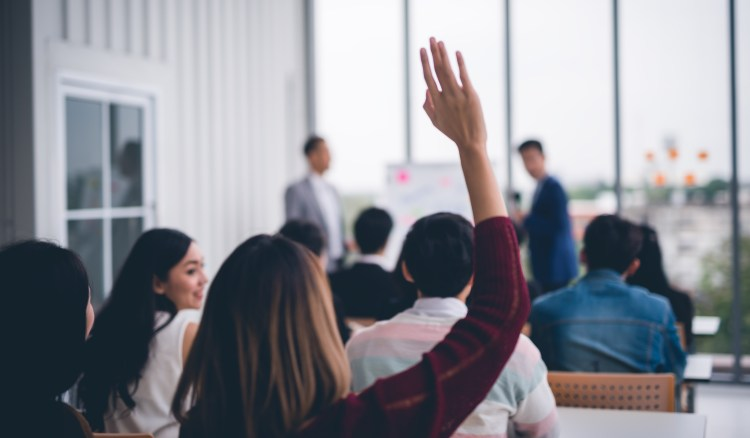 Feeling good for doing good: Why volunteering benefits everyone. Image of woman raising her hand in an office environment to volunteer