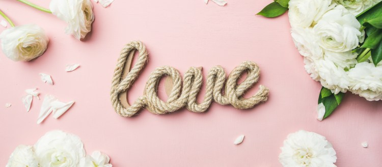 4 Tips to reduce wedding planning stress. Image of Saint Valentines Day background. Flat-lay of white ranunculus flowers and word love over light pink background, top view, wide composition. Greeting card or wedding invitation
