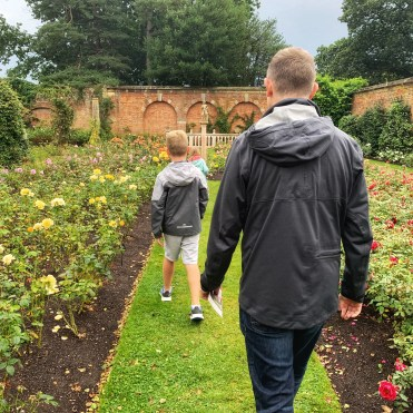 An adult & children walking in the gardens at Hever Castle