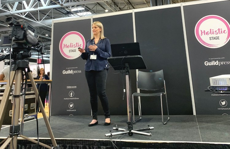 Alison Swift, author of My Wellness Toolbox, speaking on a stage at an event