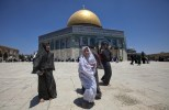 Muslim girls chat as others gather outside the Dome of the Rock at the Al-Aqsa Mosque compound in Jerusalem for the first Friday prayers of the Muslim holy fasting month of Ramadaan on July 12, 2013