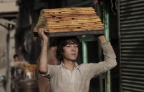 An Afghan worker carries sweets at a traditional factory ahead of the Islamic holy month of Ramadaan in Kabul, Afghanistan, on July 9, 2013