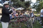 Trumpeter calls bike riders.