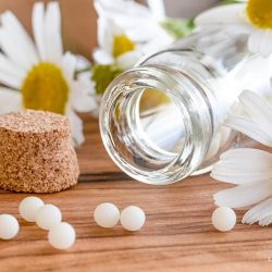 A bottle of homeopathic pills with chamomile flowers on a wooden table