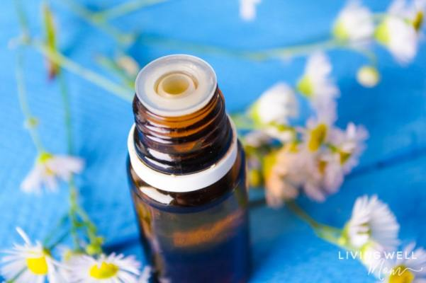 bottle of essential oil for allergies on blue table with flowers