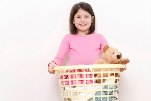 girl holding laundry basket for back to school organization
