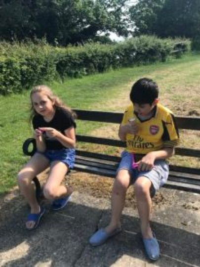Jude and Elsa sitting on a bench eating ice cream