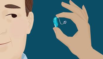 man-holding-hearing-aid