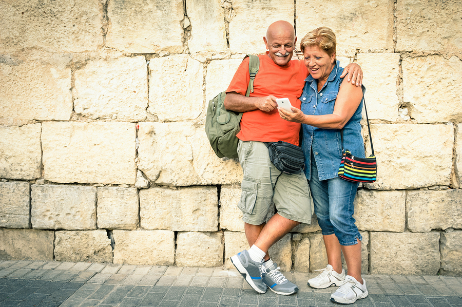 Happy senior couple having fun with a modern smartphone - Concept of active elderly and interaction with new technologies - Travel lifestyle without age limitation