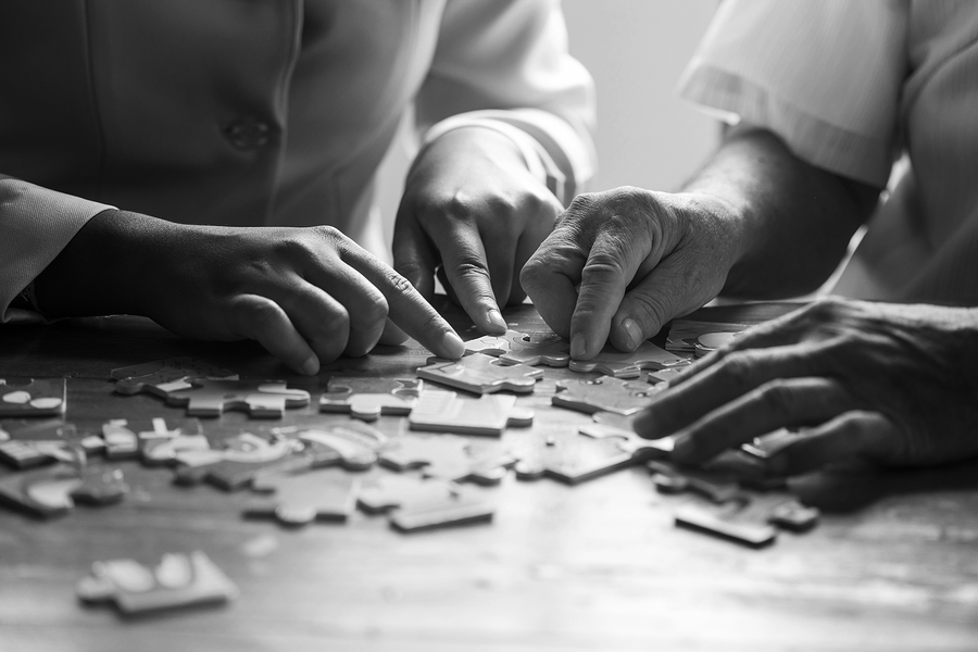 Nurse helps the senior man jigsaw puzzle to solve in a nursing home black and white