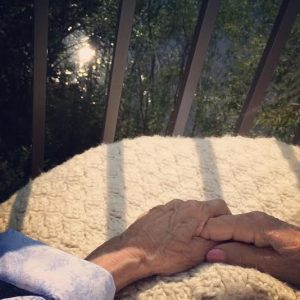 My grandma's hands on her handmade afghan, overlooking the pond at hospice.
